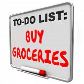 picture of reminder  - Buy Groceries words written on a dry erase board to remind you to shop for food and other items at sa super market or store - JPG