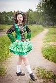 stock photo of cross-dress  - Young beautiful girl in irish dance dress and wig posing outdoor - JPG