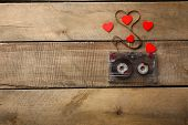 image of magnetic tape  - Audio cassette with magnetic tape in shape of heart on wooden background - JPG