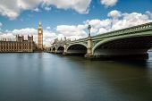 image of westminster bridge  - Big Ben and the Houses of Parliament in London with Westminster Bridge and the River Thames in the foreground against a blue sky with fluffy white clouds - JPG