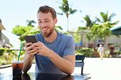 stock photo of sms  - Man on cafe using smart phone app text messaging sms drinking iced coffee in summer - JPG