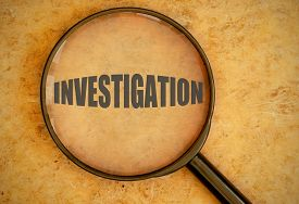 stock photo of investigation  - Magnifying glass focused on the word investigation - JPG