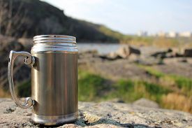 pic of thermos  - Thermos travel cup on nature background - JPG