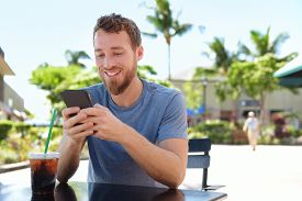 foto of cafe  - Man on cafe using smart phone app text messaging sms drinking iced coffee in summer - JPG