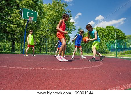 Boys and girl play basketball game on playground