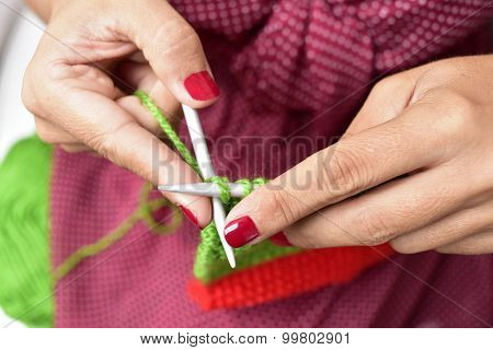 closeup of a young woman hand knitting with green yarn