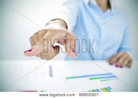 closeup of a businesswoman sitting at her desk, full of charts, pointing with her finger the way out