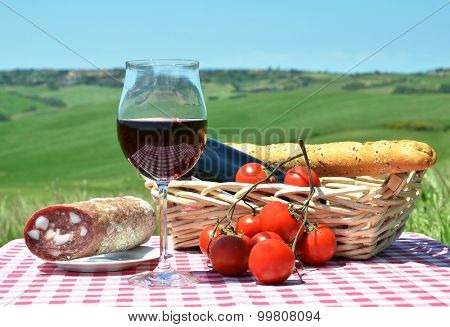 Red wine, bread and tomatos on the chequered cloth against Tuscan landscape. Italy