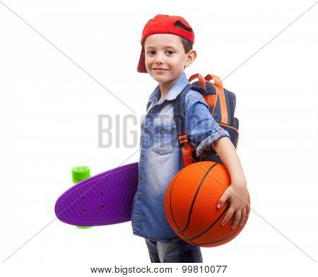 Happy school kid holding a skateboard and a basketball on white background
