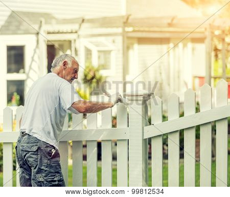 Active senior man painting a white picket fence with Instagram style filter