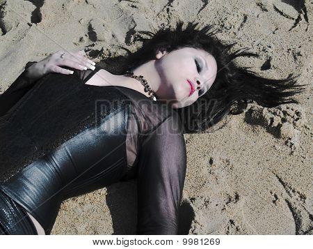 Joven mujer tendida en la arena