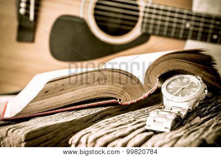 Watch And Guitar With Open Book On Old Wooden Table, Vintage Style.