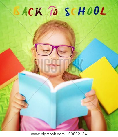 Cute little schoolgirl doing homework, lying down on the floor at home and reading book, text on the floor : back to school