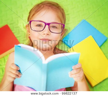 Little girl lying down on the floor at home and with pleasure reading book, wearing glasses, doing homework, back to school