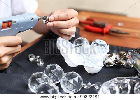 Woman Fixing Crystal Lamps With Glue Gun