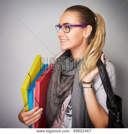 Portrait of nice blond student girl wearing glasses and looking in side, holding in hands folders and bag isolated on gray background