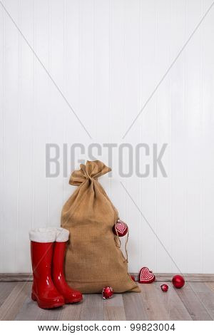 Red christmas presents with santa boots and sack on white wooden wall for decoration.