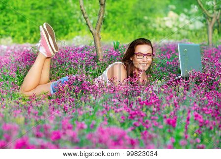 Student girl in the park, lying down on beautiful fresh flowers field and working on laptop, chatting in internet, learning in higher education