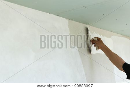 Plasterer Spreading Plaster To Wall