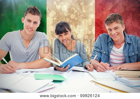 Students doing work together as they all look into the camera against italy flag in grunge effect