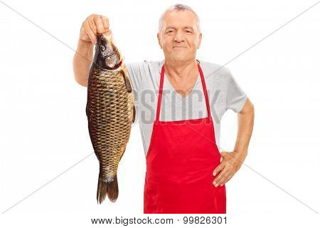 Mature fishmonger in a red apron holding a large freshwater fish and looking at the camera isolated on white background