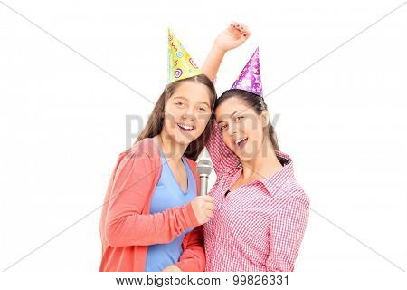 Two teenage girls with party hats singing on a microphone and looking at the camera isolated on white background
