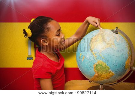 Happy pupil with globe against spain national flag