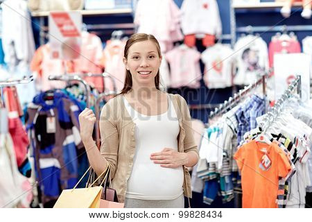 pregnancy, people, sale and expectation concept - happy pregnant woman with shopping bags at children clothing store