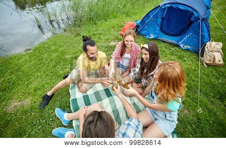 camping, travel, tourism, hike and people concept - happy friends with glass bottles drinking cider or beer at campsite