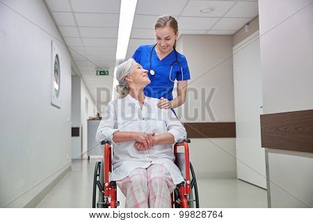 medicine, age, support, health care and people concept - happy nurse taking senior woman patient in wheelchair at hospital corridor
