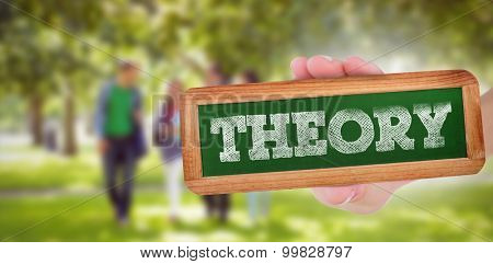 The word theory and hand showing chalkboard against froup of college students walking in the park