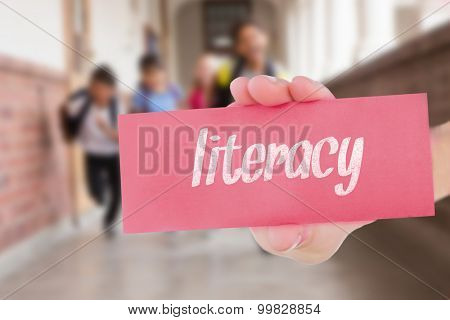 The word literacy and hand showing card against teacher helping pupils in library