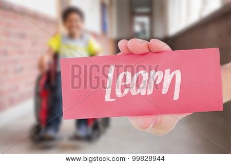 The word learn and hand showing card against teacher helping pupils in library