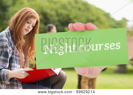 The word night courses and hand showing card against pretty student studying outside on campus