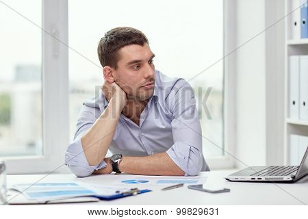 business, people and technology concept - bored businessman with laptop computer and papers at office