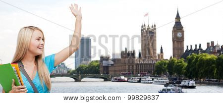 education, school, study abroad, gesture and people concept - smiling student with folders waving hand over london city and thames river background