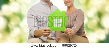family, relations, real estate, age and people concept - close up of happy senior couple with green paper house cutout over natural background