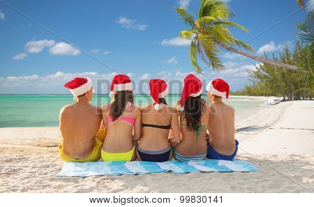 friendship, summer vacation, holidays, travel and people concept - group of friends in santa helper hats sitting on beach