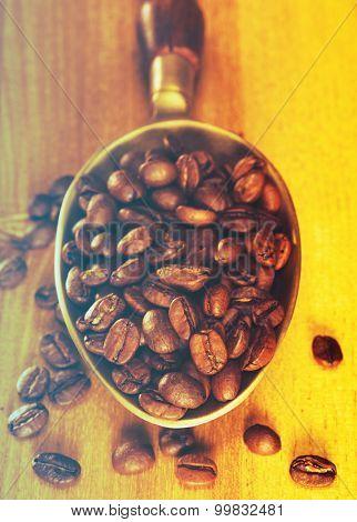 Coffee beans on wood board in metal scoop. Filtered image: vintage effect.