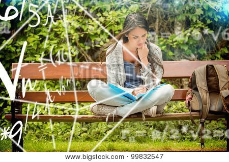 Math problems against smiling student sitting on bench reading book