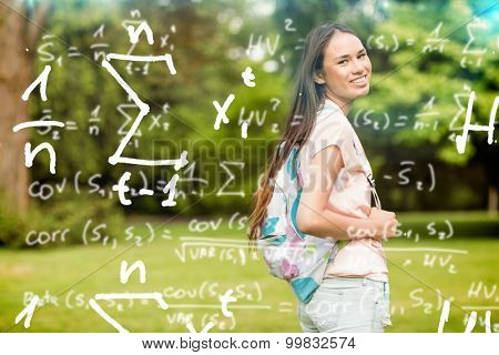 Maths equations against portrait of a smiling student with a shoulder bag