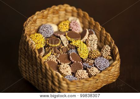 Colourful dark brown chocolate dragees in basket