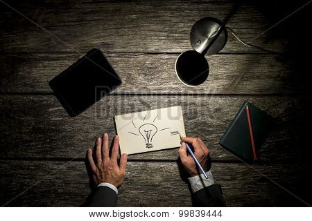 Overhead View Of A Businessman Working Late At His Table By The Light Of A Desk Lamp Creating New Id