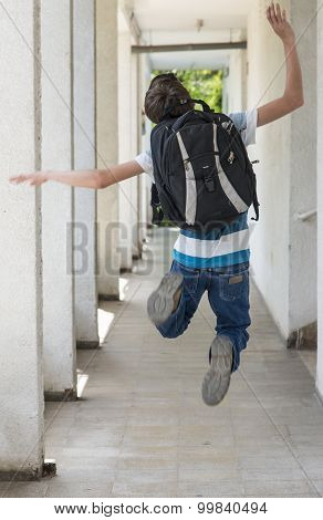 Teenage school boy with a backpack on his back junping