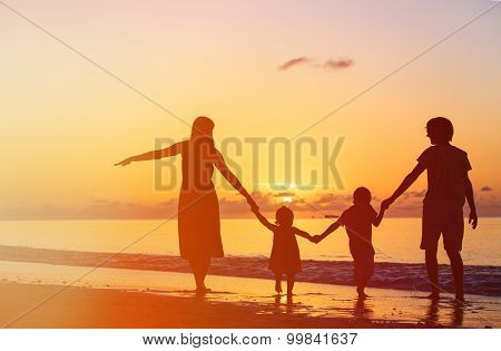 happy family with two kids having fun at sunset