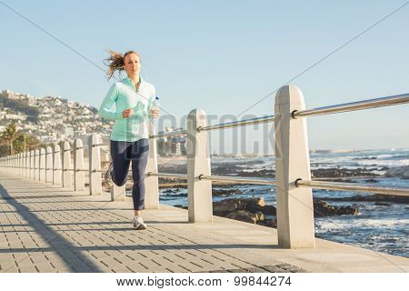 Focused fit blonde jogging at promenade on a sunny day