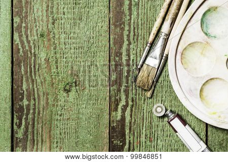 Paint brushes set and a palette with oil paint tubes on a green wooden background