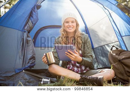 Portrait of pretty blonde camper using tablet and holding cup while sitting in tent