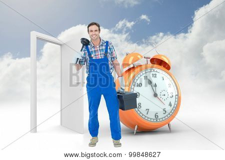 Portrait of plumber holding plunger and tool box against alarm clock counting down to twelve