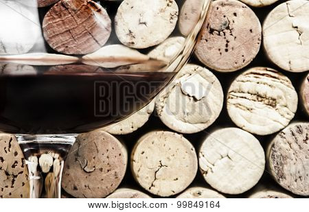 Close-up of red wine glass on wine corks background in the horizontal format